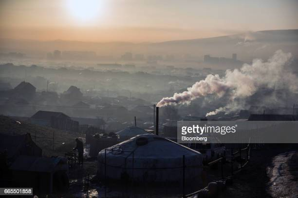 Smoke rises from chimneys in a ger district at sunrise in Ulaanbaatar Mongolia on Tuesday March 14 2017 The subzero winters in Ulaanbaatar force...