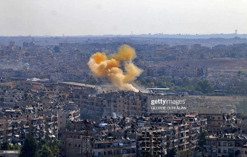 TOPSHOT - Smoke rises from reported opposition fire from buildings in an eastern government-held neighbourhood of the northern Syrian city of Aleppo on October 20, 2016 as clashes erupted in an area designated as a humanitarian corridor for civilians to leave the embattles city, an AFP journalist said, despite an announced pause in the Syrian army's Russian-backed offensive. OURFALIAN