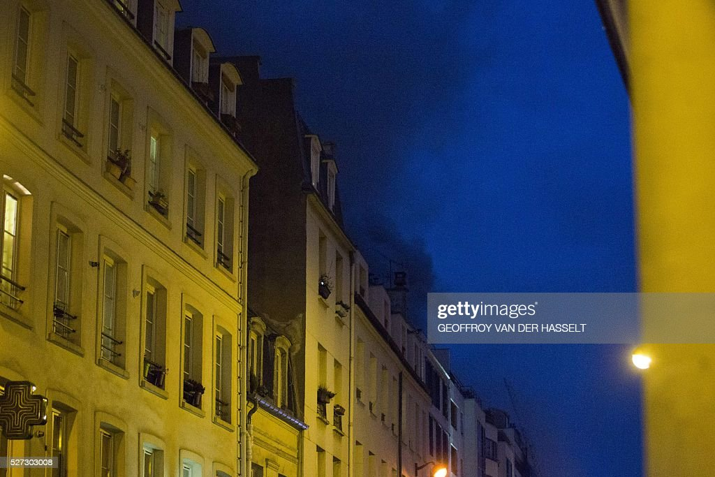 Smoke rises from the roof of a building on rue de Charonne in Paris after it caught fire on May 2, 2016. 180 firefighters were deployed to contain the fire in the six-storey building in which textiles and furniture are stored, according to the fire brigade. Two people, including one firefighter, were injured in the blaze. / AFP / GEOFFROY