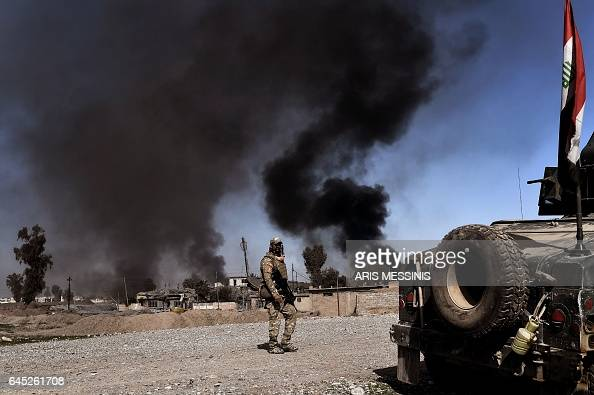 TOPSHOT Smoke rises in the background as members of Iraq's elite Rapid Response Division hold position in the northern city of Mosul as they continue...
