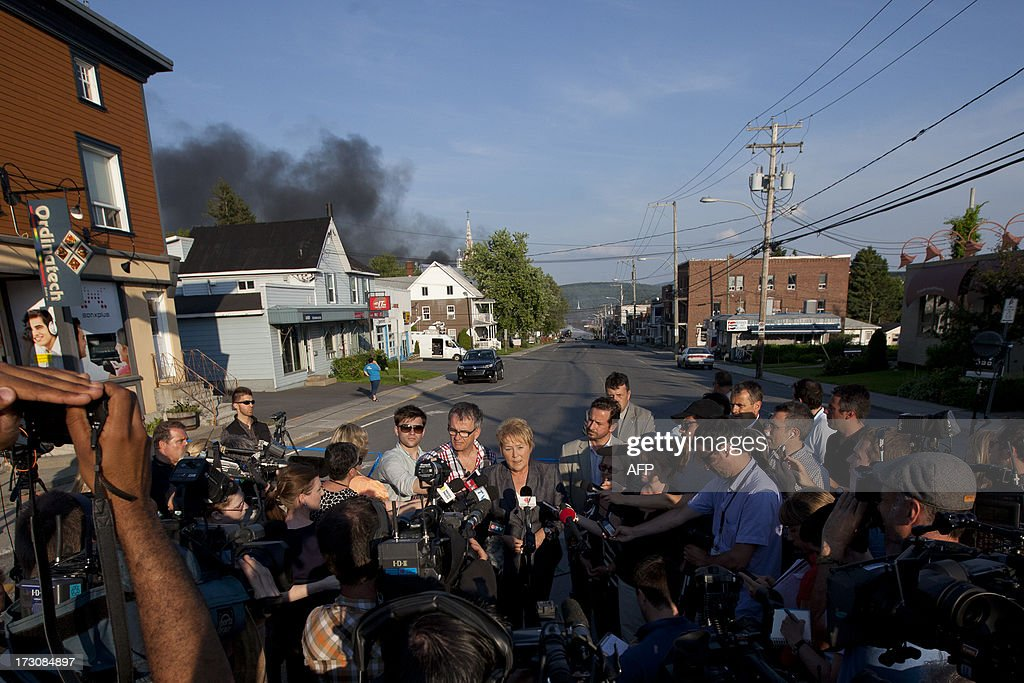 Smoke rises in the background as Quebec Prime Minister Pauline Marois speaks to reporters after a freight train loaded with oil derailed in Lac...