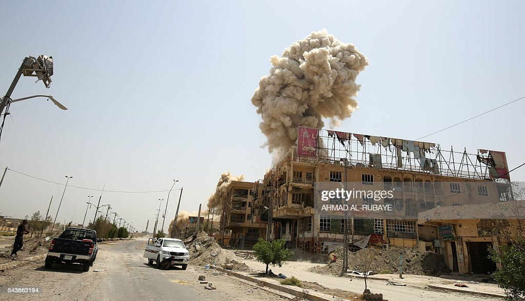 Smoke rises in the city of Fallujah on June 30, 2016 as Iraqi forces destroy a booby-trapped building after they've recaptured the city from Islamic State (IS) group jihadists. Iraqi forces have retaken full control of Fallujah, a longtime jihadist bastion just 50 kilometres (30 miles) west of Baghdad, after a vast operation that was launched in May. / AFP / AHMAD