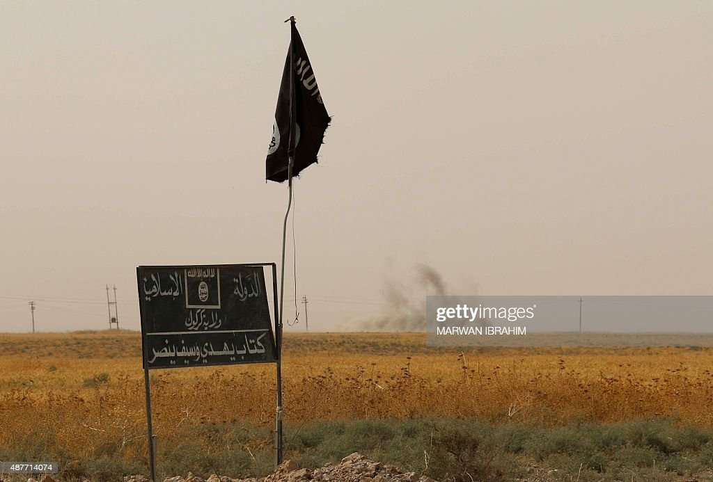 Smoke rises in the distance behind an Islamic State (IS) group flag and banner after Iraqi Kurdish Peshmerga fighters reportedly captured several villages from IS group jihadists in the district of Daquq, south of the northern Iraqi multi-ethnic city of Kirkuk on September 11, 2015. An Iraqi officer said that the operation was launched in the morning with support from international coalition aircraft, and has succeeded in retaking ten villages from IS. IBRAHIM
