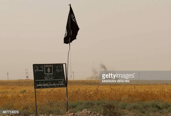 Smoke rises in the distance behind an Islamic State group flag and banner after Iraqi Kurdish Peshmerga fighters reportedly captured several villages...