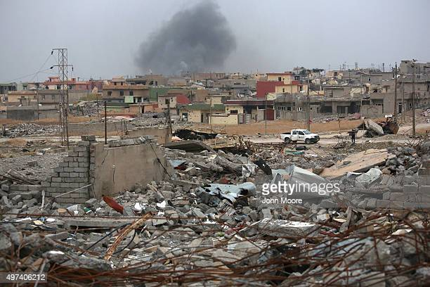 Smoke rises in the distance on a day when ISIL fighters fired multiple Katyusha rockets at Kurdish Peshmerga forces occupying the ruins of the town...