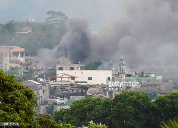 TOPSHOT Smoke rises near a public market after military attack helicopters fired rockets on the positions of Muslim extremists in Marawi on the...