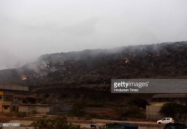 Smoke rising out garbage hills due to fire causing pollution at Bhalswa landfill on September 21 2017 in New Delhi India Bhalswa landfill site is...