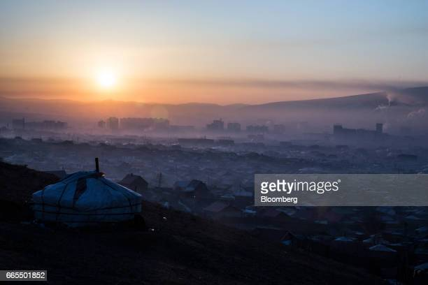 Smoke rises over a ger district at sunrise in Ulaanbaatar Mongolia on Tuesday March 14 2017 The subzero winters in Ulaanbaatar force residents burn...