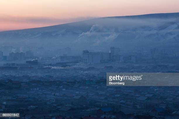 Smoke rises over a ger district in Ulaanbaatar Mongolia on Tuesday March 14 2017 The subzero winters in Ulaanbaatar force residents burn raw coal for...