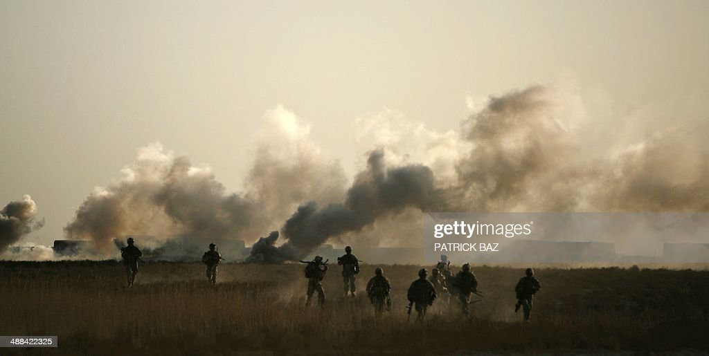A smoke screen billows in the background as US Marines with 1/3 Marine Charlie company retreat after battling Taliban fire in Trikh Nawar a poppy...