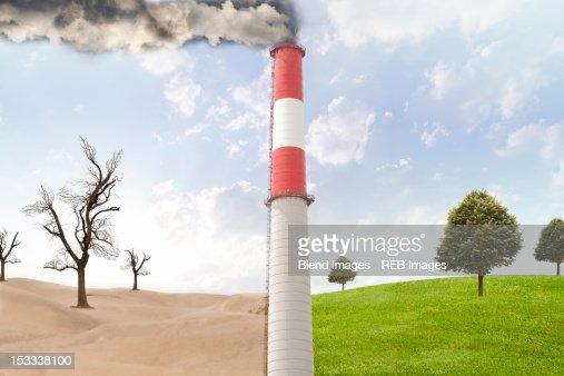 Smoke stack between desert and rural field : Stock Photo