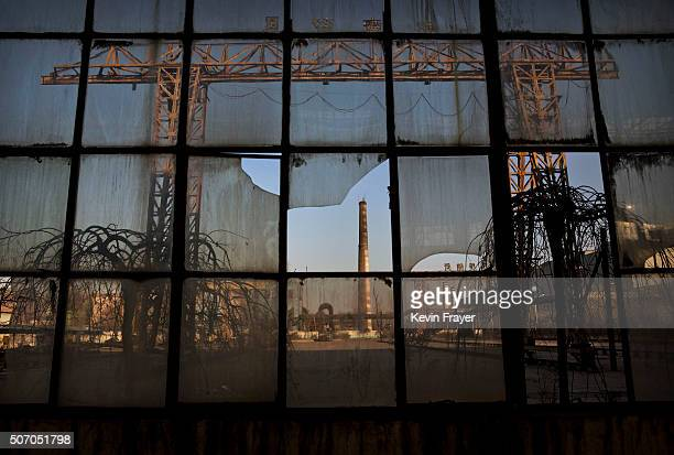 A smoke stack is seen through a broken window of a building in the abandoned Qingquan Steel plant which closed in 2014 and became one of several...