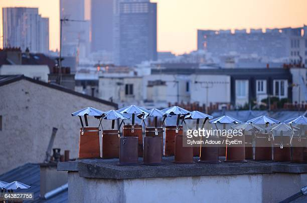 Smoke Stacks On Buildings In City At Dusk
