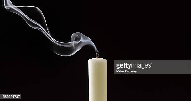Smoke trailing from extinguished white candle