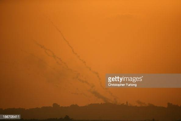 Smoke trails from a militant rocket cross the evening sky as they head into Israel on November 19 2012 on Israel's border with the Gaza Strip...