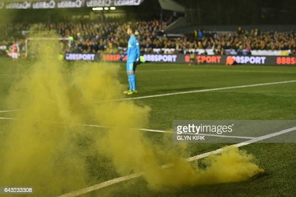 A smokebomb goes off on the pitch during the English FA Cup fifth round football match between Sutton United and Arsenal at the Borough Sports Ground...