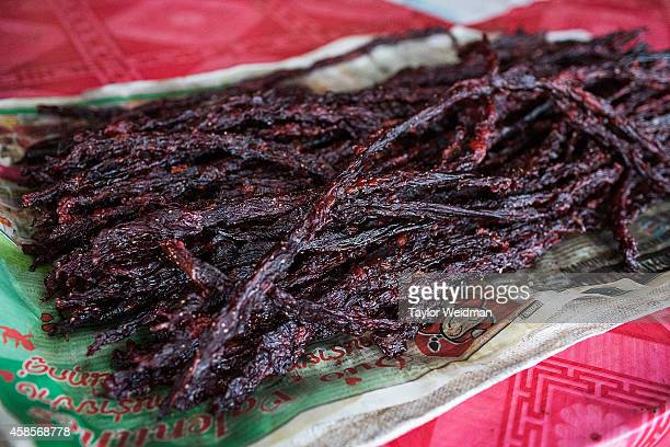 Smoked dog meat jerky is sold by a vendor on the outskirts of the Tha Rae market on November 7 2014 in Ban Tha Rae Thailand Under considerable...