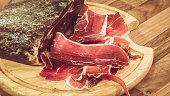 Smoked ham sliced on cutting board.