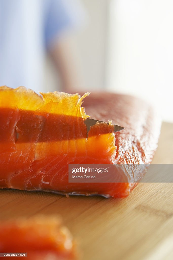 Smoked salmon being sliced on  chopping board : Stock Photo