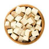 Smoked tofu cubes in wooden bowl. Bean curd. Coagulated soy milk, pressed into firm white blocks. Component of Asian cuisine. Meat substitute. Isolated macro food photo close up from above over white