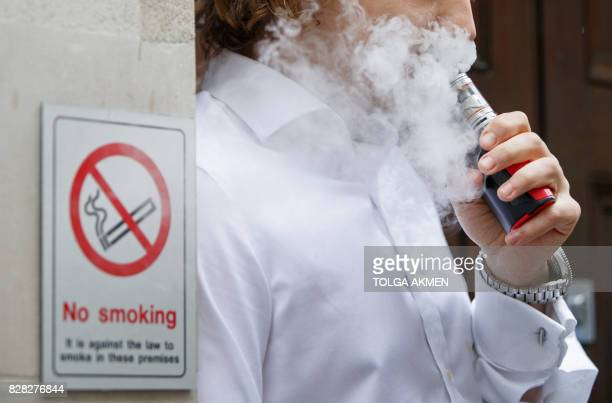 A smoker is engulfed by vapours as he smokes an electronic vaping machine during lunch time in central London on August 9 2017 World stock markets...