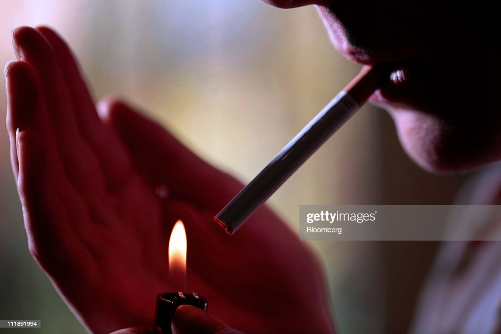 A smoker lights a cigarette with a lighter for an arranged photograph in London, U.K., on Thursday, April 7, 2011. The global market for cigarettes excluding China, which is largely closed to foreign tobacco companies, will probably shrink by 2.5 percent in 2011, BAT Chief Executive Officer Nicandro Durante said Feb. 24. Photographer: Jason Alden/Bloomberg via Getty Images