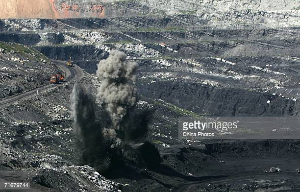 Smokes rise from coal seams after a blasting in an open pit coal mine on August 19 2006 in Chifeng of Inner Mongolia Autonomous Region China...