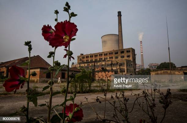 A smokestack from a coal fired power plant is seen next to an abandoned former paper factory near the site of a large floating solar farm project...