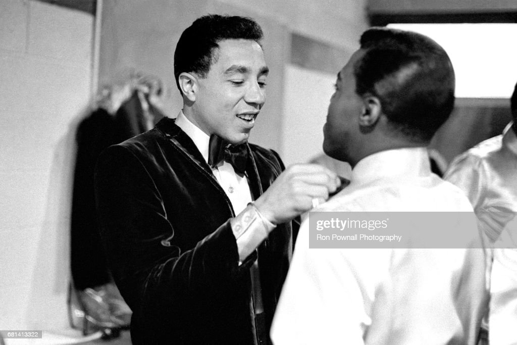 Smokey Robinson helping tie a tie of one of the Miracles in boys lockerroom before going onstage at Evanston High School in Evanston, Illinois September 1968