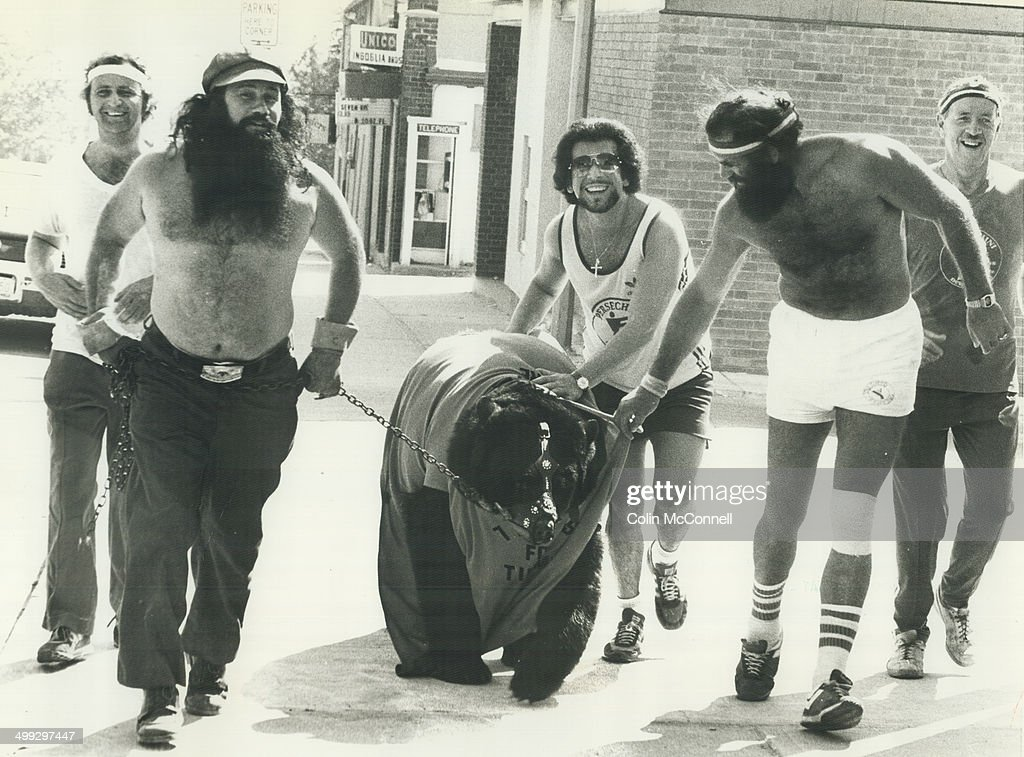 Smokey the bear jogs for charity. Smokey the Wrestling Bear is led over finish line by owner and trainer; Wild Man Dave McKigney; Bob Moffatt (left); Joe Persechini and another runner in annual 7-mile jog from Newmarket to Bradford yesterday to raise money for Ontario Society for Crippled Children. More than 100 people; organized by Persechini-a fitness centre operator at Newmarket-turned out. The goal of walk is 85;000.