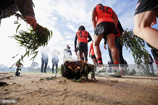 A smoking ceremony takes place for the players as they head out onto oval for training during an Essendon Bombers AFL media opportunity at True Value...