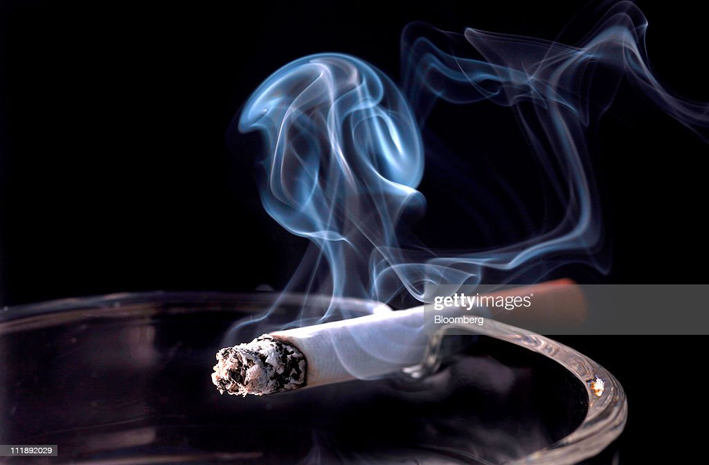 A smoking cigarette sits on the edge of an ashtray in an arranged photograph in London, U.K., on Thursday, April 7, 2011. The global market for cigarettes excluding China, which is largely closed to foreign tobacco companies, will probably shrink by 2.5 percent in 2011, BAT Chief Executive Officer Nicandro Durante said Feb. 24. Photographer: Jason Alden/Bloomberg via Getty Images