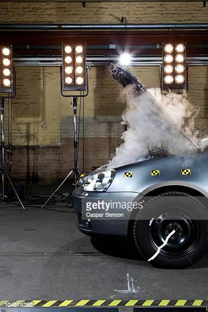 A smoking crash test car with the hood up