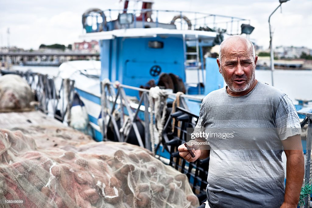 Smoking Fisherman On Quay : Stock Photo