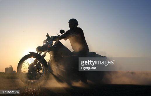 Smoking motorbike and rider sillhouetted against blue prairie sky