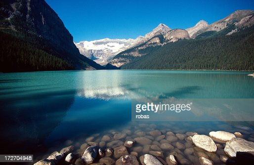 Smooth stones and still waters of Lake Louise in Banff