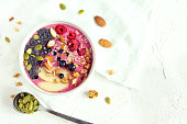 Smoothie bowl with fresh berries, nuts, seeds and homemade granola for healthy breakfast, copy space
