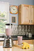 Smoothie in blender by bananas on kitchen counter