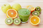 Green smoothie or juice in glass on wooden table, detox and diet food, healthy breakfast