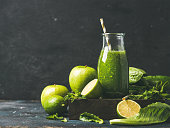 Green smoothie with apple, romaine lettuce, lime and mint, dark blue background, selective focus, copy space. Detox, dieting, clean eating, vegetarian, vegan, fitness diet or healthy lifestyle concept