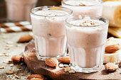 Smoothie with banana, yogurt, oatmeal and nuts, selective focus