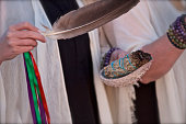 Smudging with women holding burning herbs and feather