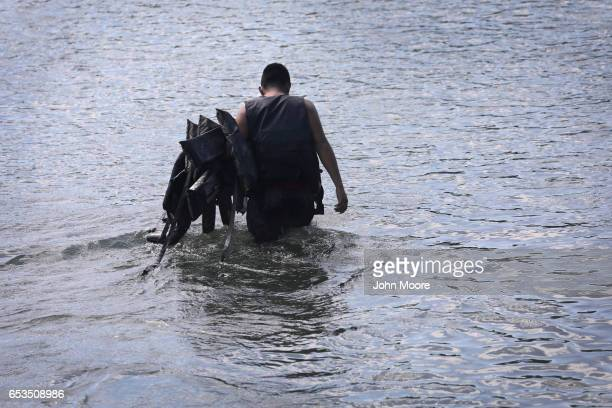 A smuggler also known as a 'coyote' carries life jackets while walking a group of undocumented immigrants across the shallow Rio Grande at the...