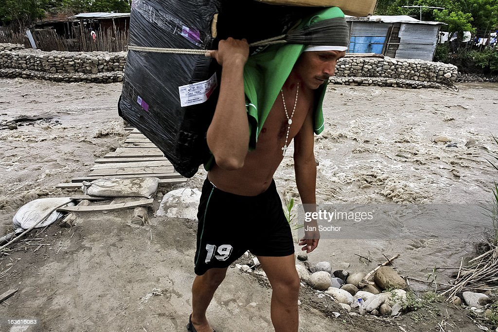 A smuggler carries a huge box full of the Colombian contraband on the foot bridge across the river Tachira on the Colombia-Venezuela border, on 2 May 2006 in La Parada, Colombia. Venezuelan gasoline, being 20 times cheaper than in Colombia, is the most wanted smuggling item, followed by food and car parts, while reputable Colombian clothing flow to Venezuela. There are about 25,000 barrels of gasoline crossing illegally the Venezuelan border every day. The risky contraband smuggling, especially during the rainy season when the river rises, makes a living to hundreds of poor families in communities on both sides of the frontier.