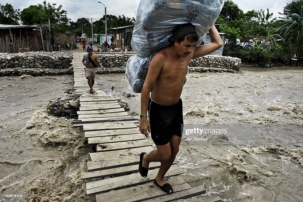 A smuggler carries a huge pack full of the Colombian contraband on the foot bridge across the river Tachira on the Colombia-Venezuela border, on 2 May 2006 in La Parada, Colombia. Venezuelan gasoline, being 20 times cheaper than in Colombia, is the most wanted smuggling item, followed by food and car parts, while reputable Colombian clothing flow to Venezuela. There are about 25,000 barrels of gasoline crossing illegally the Venezuelan border every day. The risky contraband smuggling, especially during the rainy season when the river rises, makes a living to hundreds of poor families in communities on both sides of the frontier.