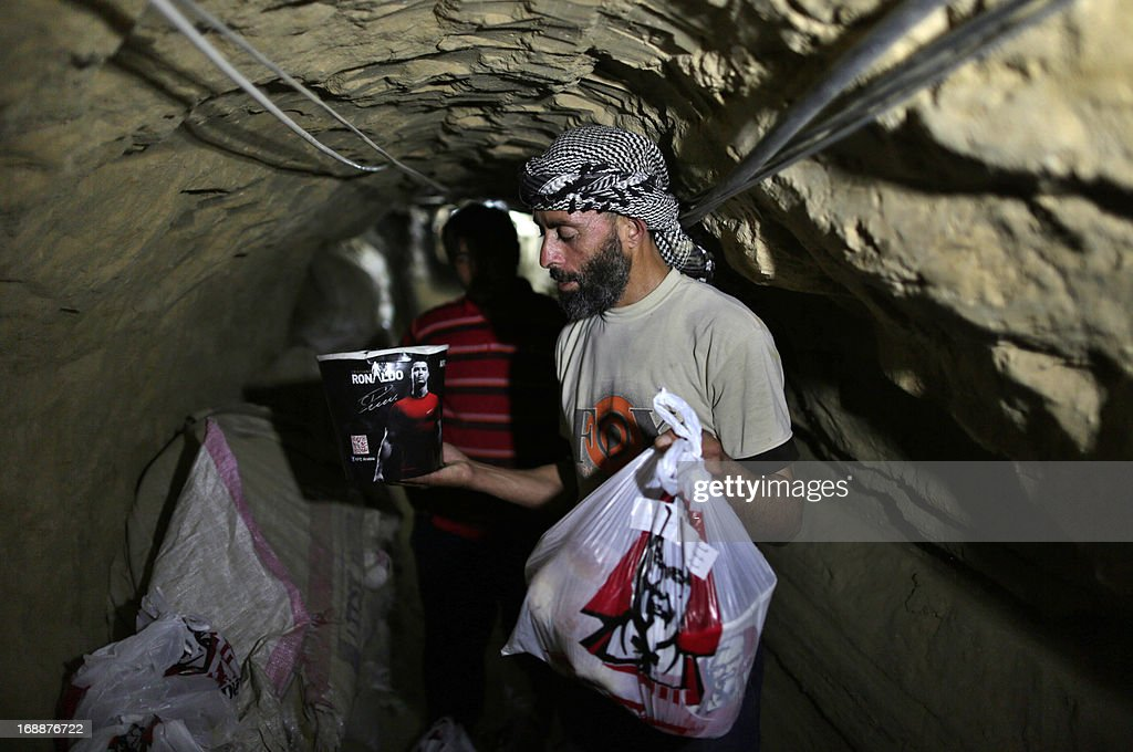 A smuggler carries food from Kentucky Fried Chicken to be delivered through an underground tunnel linking the Gaza Strip to Egypt, on May 13, 2013 in Rafah. Fast food is just the latest trend for smugglers seeking to turn a buck by bringing in hard-to-get products to the Gaza Strip, which has been under an Israeli blockade since 2007. It's not exactly 'fast' -- taking several hours to arrive, with the Palestinian delivery company behind it charging hefty prices to cover the cost of fuel and transport.