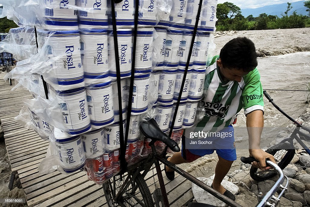 A smuggler pushes a bicycle loaded with contraband on the foot bridge across the river Tachira on the Colombia-Venezuela border, on 2 May 2006 in La Parada, Colombia. Venezuelan gasoline, being 20 times cheaper than in Colombia, is the most wanted smuggling item, followed by food and car parts, while reputable Colombian clothing flow to Venezuela. There are about 25,000 barrels of gasoline crossing illegally the Venezuelan border every day. The risky contraband smuggling, especially during the rainy season when the river rises, makes a living to hundreds of poor families in communities on both sides of the frontier.