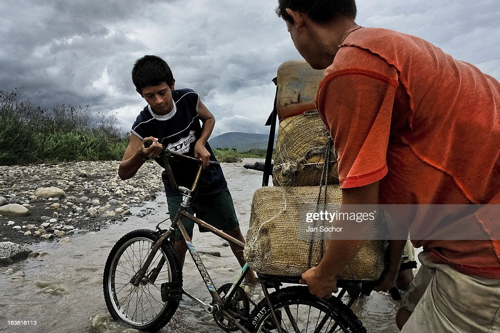 Smugglers push a bicycle loaded with gasoline barrels on the shore of the river Tachira on the Colombia-Venezuela border, on 3 May 2006 in La Parada, Colombia. Venezuelan gasoline, being 20 times cheaper than in Colombia, is the most wanted smuggling item, followed by food and car parts, while reputable Colombian clothing flow to Venezuela. There are about 25,000 barrels of gasoline crossing illegally the Venezuelan border every day. The risky contraband smuggling, especially during the rainy season when the river rises, makes a living to hundreds of poor families in communities on both sides of the frontier.