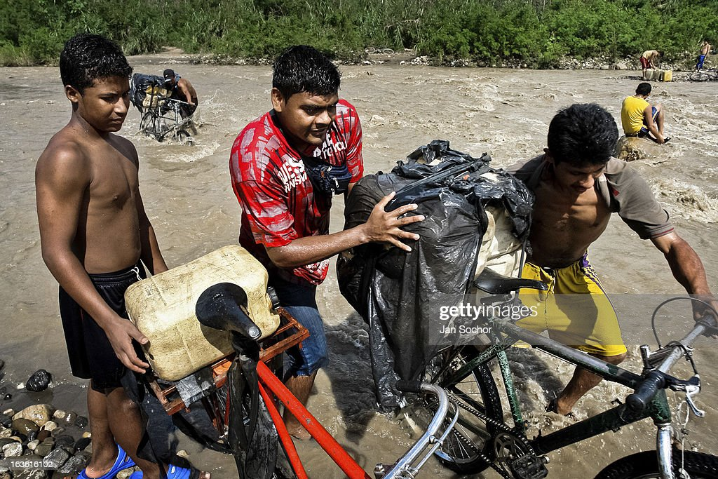 Smugglers push bicycles loaded with gasoline barrels on the shore of the river Tachira on the Colombia-Venezuela border, on 2 May 2006 in La Parada, Colombia. Venezuelan gasoline, being 20 times cheaper than in Colombia, is the most wanted smuggling item, followed by food and car parts, while reputable Colombian clothing flow to Venezuela. There are about 25,000 barrels of gasoline crossing illegally the Venezuelan border every day. The risky contraband smuggling, especially during the rainy season when the river rises, makes a living to hundreds of poor families in communities on both sides of the frontier.