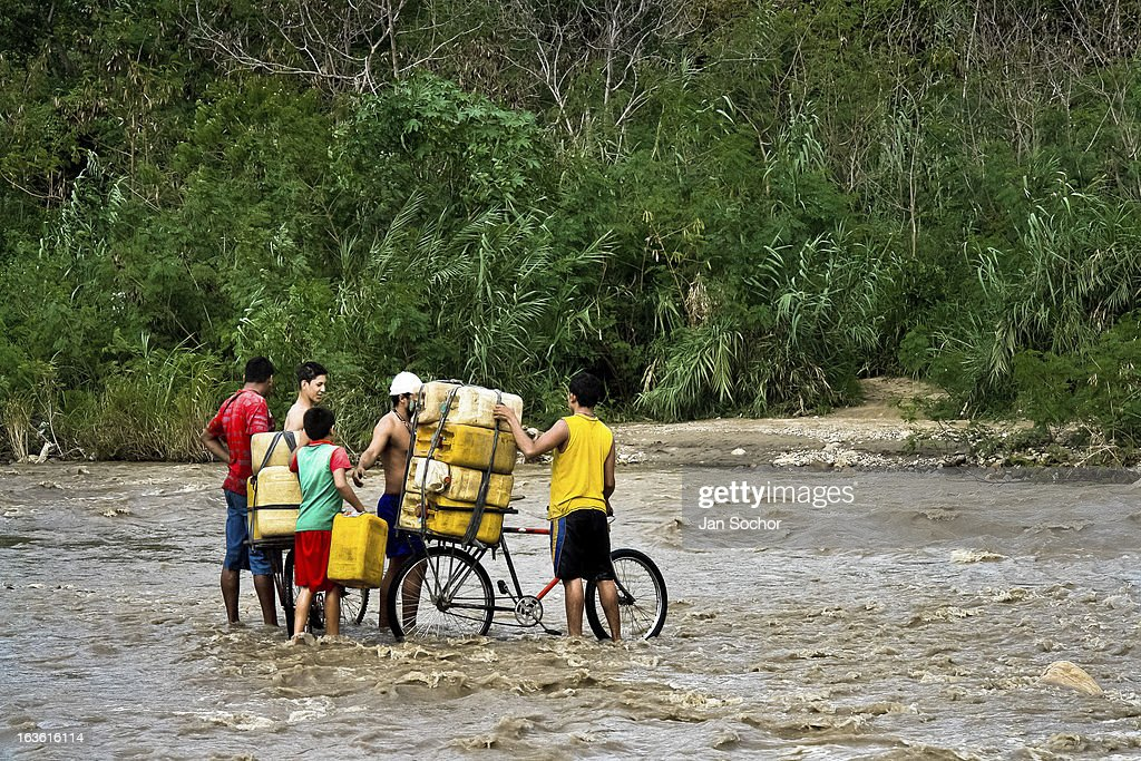 Smugglers push bicycles loaded with gasoline barrels through the river Tachira on the Colombia-Venezuela border, on 2 May 2006 in La Parada, Colombia. Venezuelan gasoline, being 20 times cheaper than in Colombia, is the most wanted smuggling item, followed by food and car parts, while reputable Colombian clothing flow to Venezuela. There are about 25,000 barrels of gasoline crossing illegally the Venezuelan border every day. The risky contraband smuggling, especially during the rainy season when the river rises, makes a living to hundreds of poor families in communities on both sides of the frontier.
